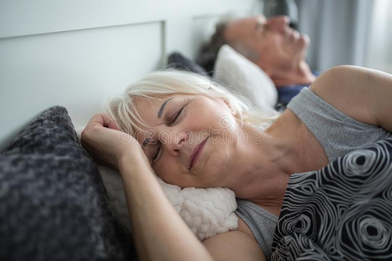 Senior lady sleeping in comfortable bed with husband stock photography
