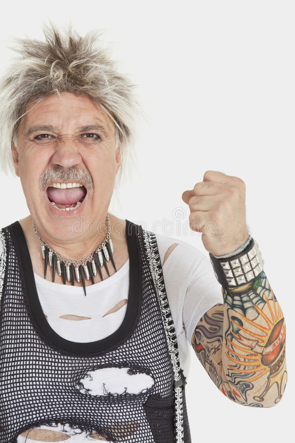 Download Portrait Of Senior Male Punk Screaming With Clenched Fist Over Gray Background Stock Photo - Image: 30851982