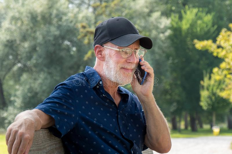Portrait of senior man with beard and glasses using smartphone stock photos