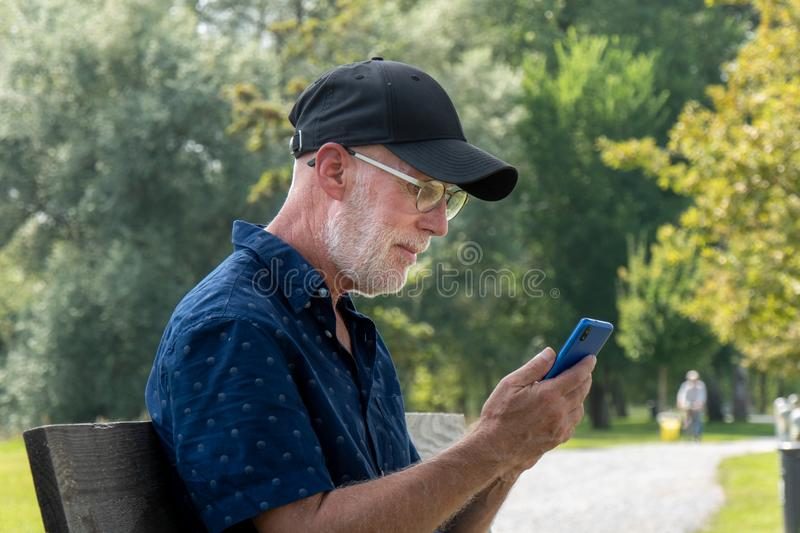 Portrait of senior man with beard and glasses using smartphone royalty free stock photos