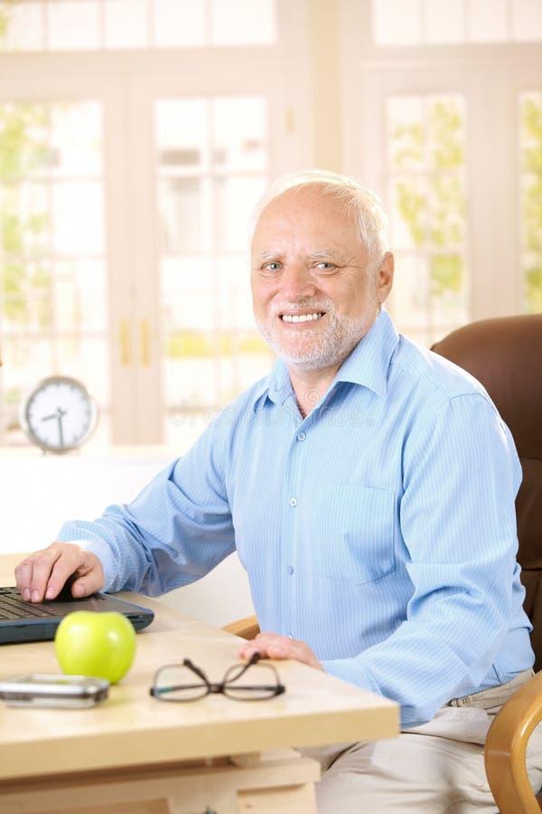 Portrait of senior man at desk stock photos
