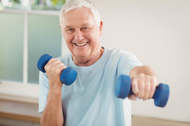 Portrait of senior man exercising with dumbbells stock images