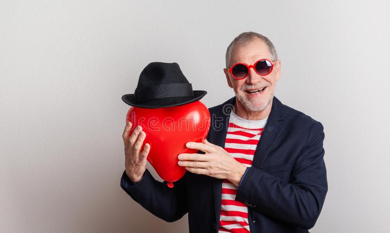 Portrait of a senior man in love in a studio, holding a red heart balloon. royalty free stock photos