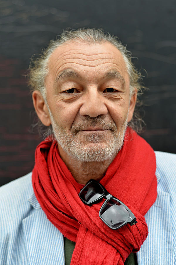 Portrait of senior man. With oriental eyes with grey beard and red scarf stock photo