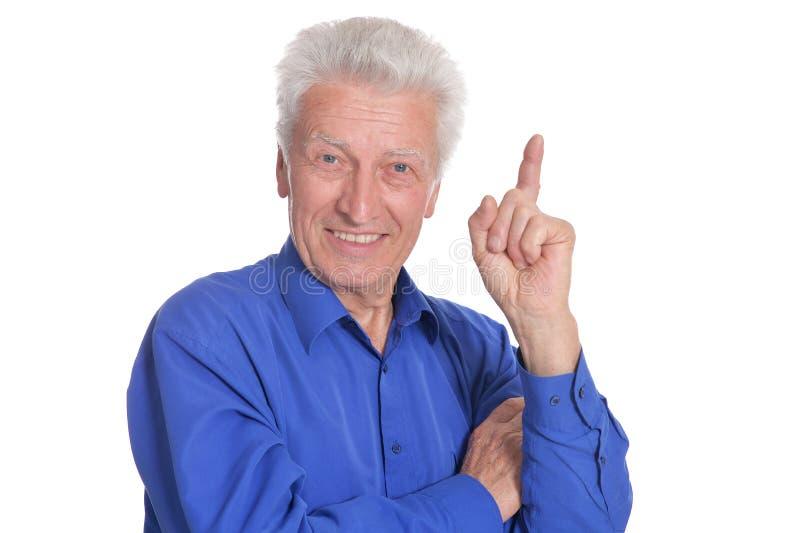 Portrait of senior man pointing upward on white background stock photos