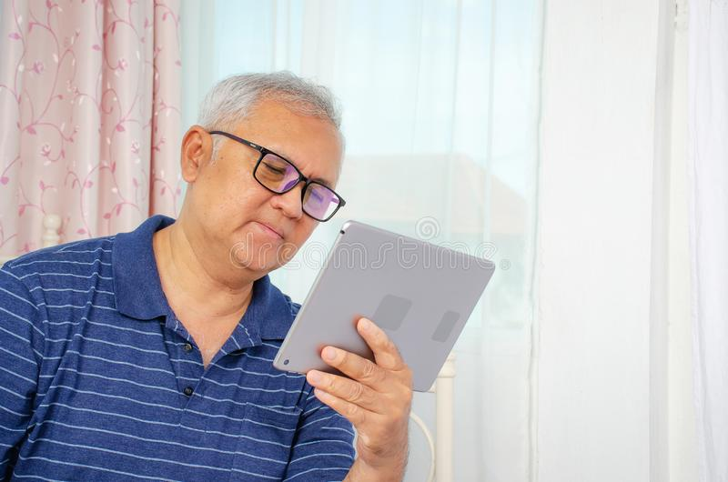 Portrait of senior man reading news on digital tablet. Serious mature male using portable computer at home, copy space. A Portrait of senior man reading news on royalty free stock photos