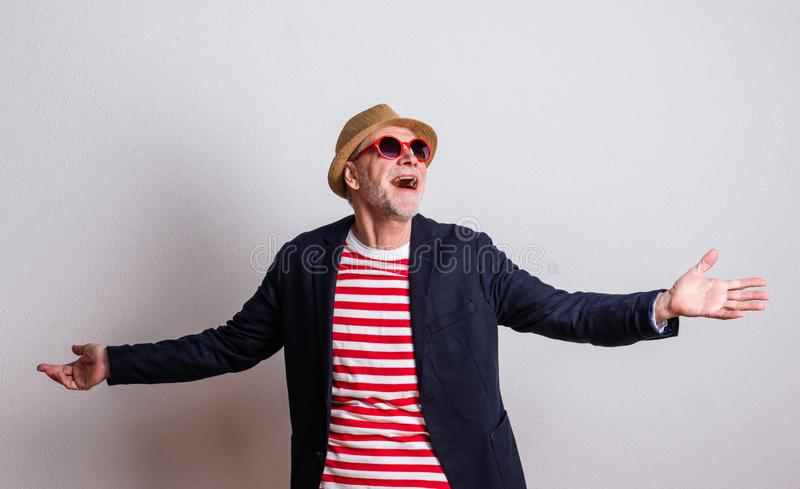 Portrait of a senior man with red sunglasses in a studio, arms stretched. stock image