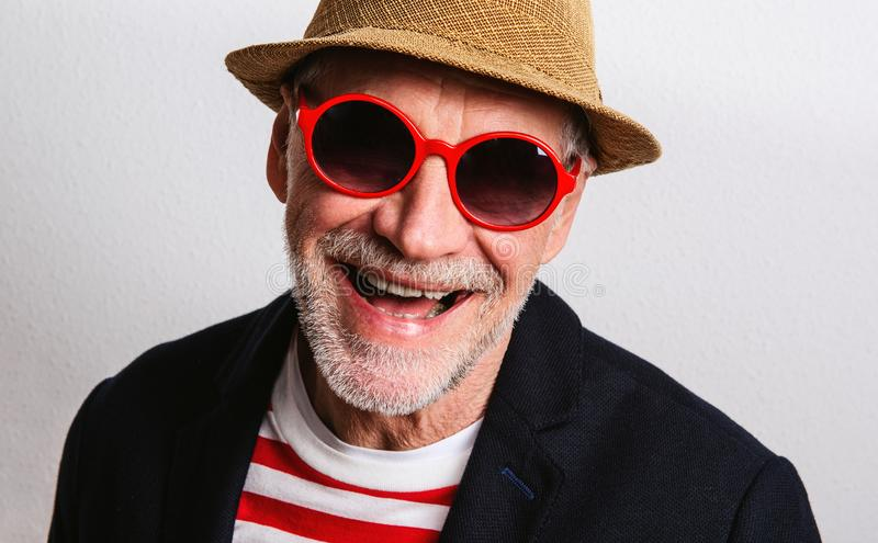 Portrait of a senior man with red sunglasses in a studio, headshot. royalty free stock photography