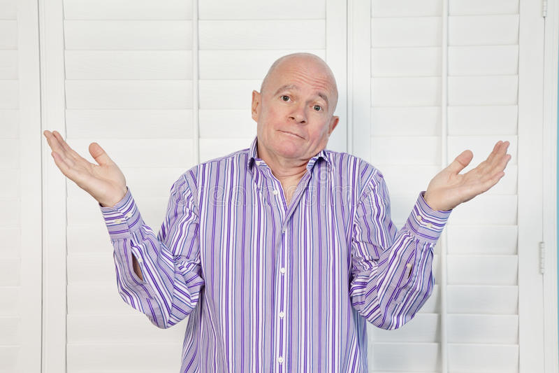 Portrait of a senior man shrugging shoulders in confusion stock photos