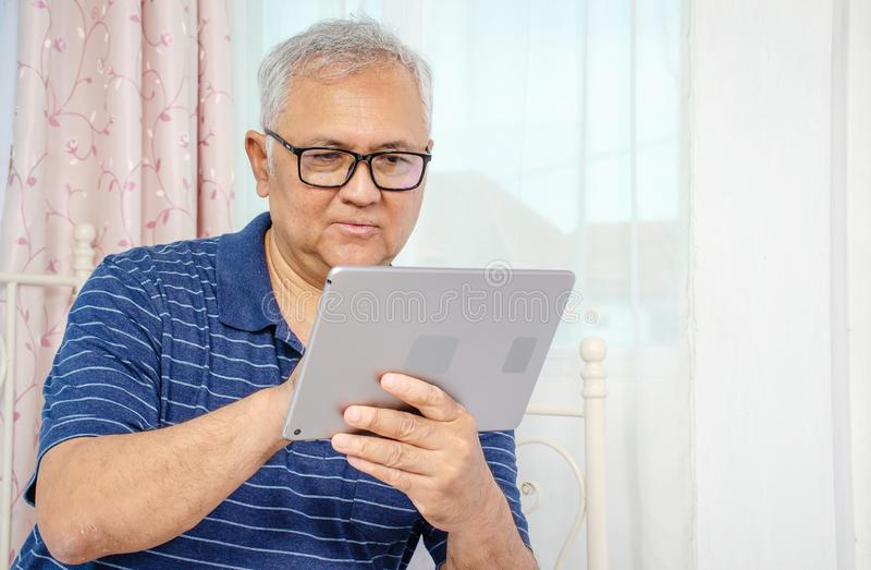 Portrait of senior man sitting at sofa at home and reading news on digital tablet stock photo