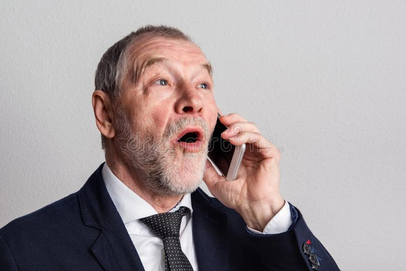 Portrait of a senior man with smartphone in a studio, making phone call. stock images
