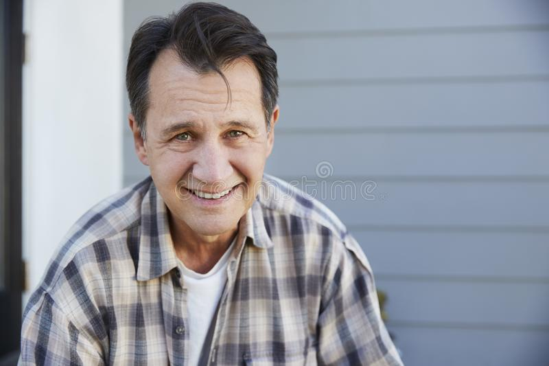 Portrait Of Senior Man Standing Outside Grey Clapboard House royalty free stock photo
