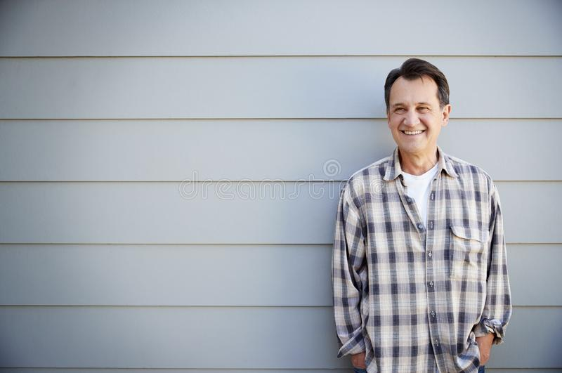 Portrait Of Senior Man Standing Outside Grey Clapboard House stock images