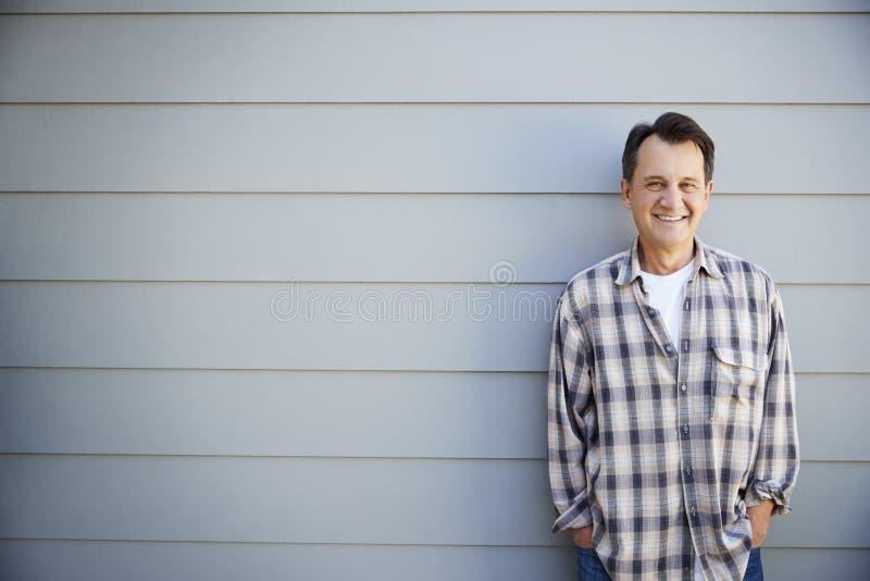 Portrait Of Senior Man Standing Outside Grey Clapboard House stock image