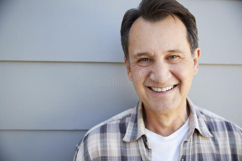 Portrait Of Senior Man Standing Outside Grey Clapboard House royalty free stock images