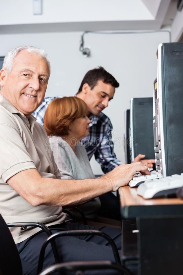 Portrait Of Senior Man Using Computer In Classroom. Portrait of senior men using computer with classmate and tutor in background at classroom royalty free stock photo