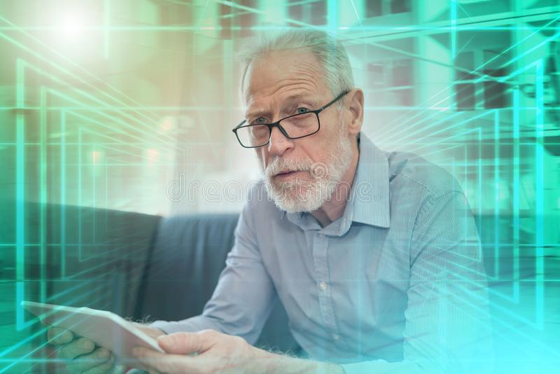 Portrait of senior man using a tablet; multiple exposure royalty free stock image