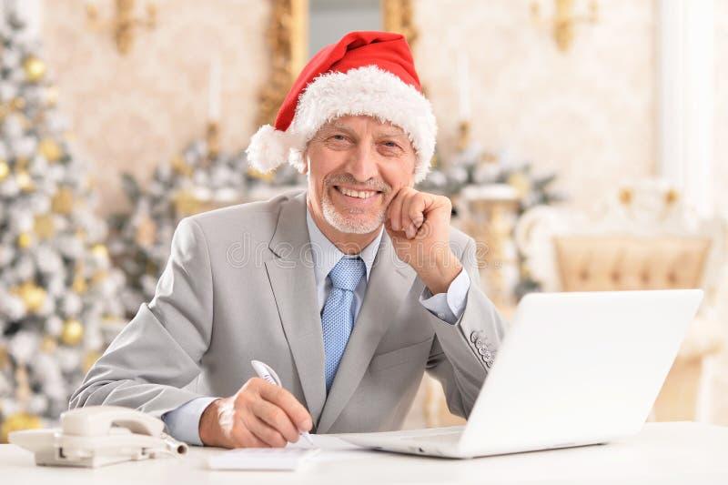 Portrait of senior man working with laptop stock photos