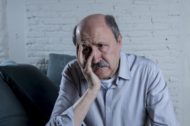 Portrait of senior mature old man on his 60s at home couch alone feeling sad and worried suffering pain and depression stock image