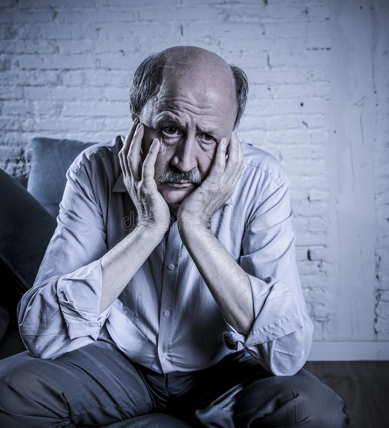 Portrait of senior mature old man on his 60s at home couch alone royalty free stock photos