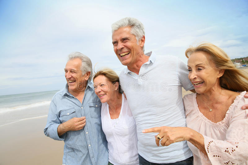 Portrait of senior people on the beach walking royalty free stock photo