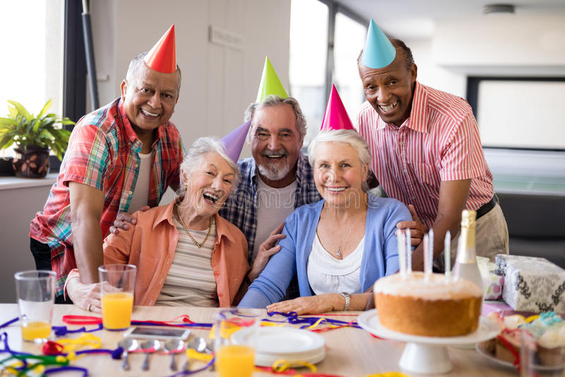 Portrait of senior people wearing party hats celebrating birthday stock photography
