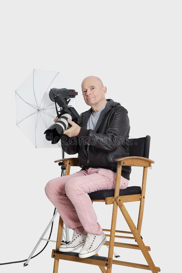 Portrait of senior photographer sitting on director's chair with camera stock images