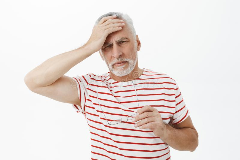 Portrait of senior retired man in striped t-shirt taking off glasses touching forehead and grimacing from pain feeling stock images