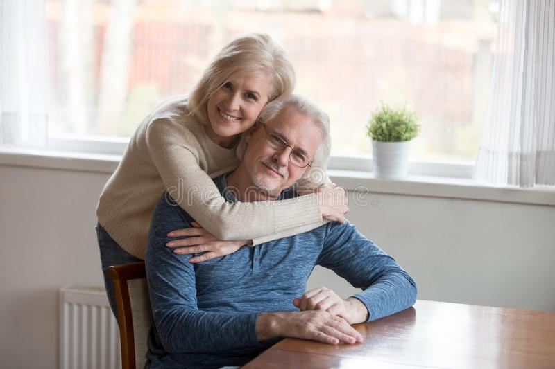 Portrait of aged happy wife hugging husband from behind. Portrait of senior smiling wife hugging loving husband from behind at home, aged happy couple embrace stock photo