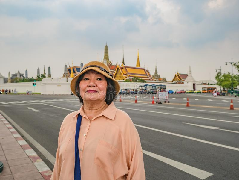 Portrait of Senior Tourist in Wat Phrakeaw Temple  with Cloud sky.Wat Phrakeaw Temple is the main Temple of bangkok stock image
