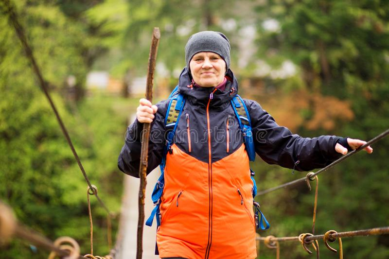 Portrait Of Senior Woman with backpack On Hike cross river royalty free stock photography