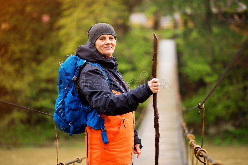 Portrait Of Senior Woman with backpack On Hike cross river stock images