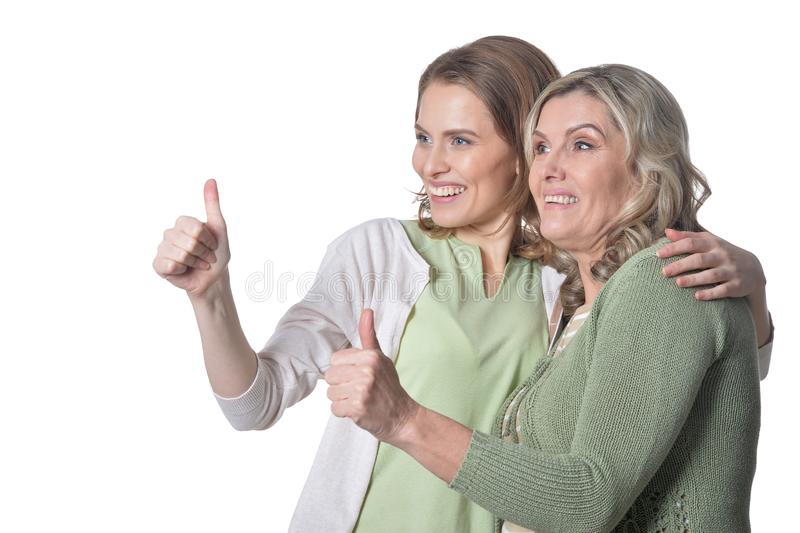 Portrait senior woman with daughter with thumbs up on white background royalty free stock images