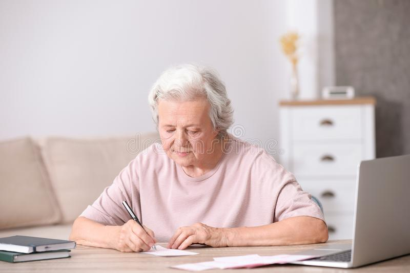 Portrait of senior woman filling out lottery ticket royalty free stock photos
