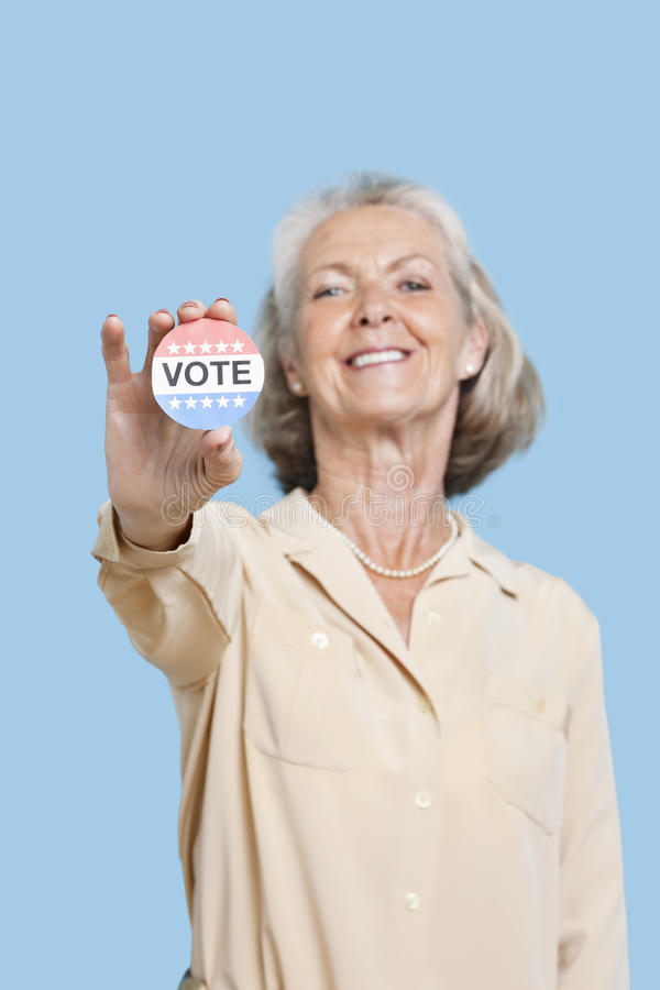 Portrait of senior woman holding an election badge against blue background