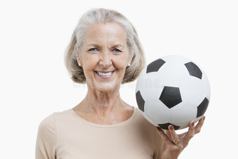 Portrait of senior woman holding soccer ball against white background stock image