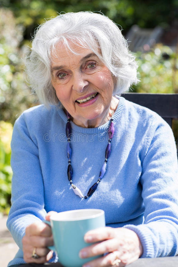 Portrait Of Senior Woman Relaxing In Garden With Hot Drink stock photo