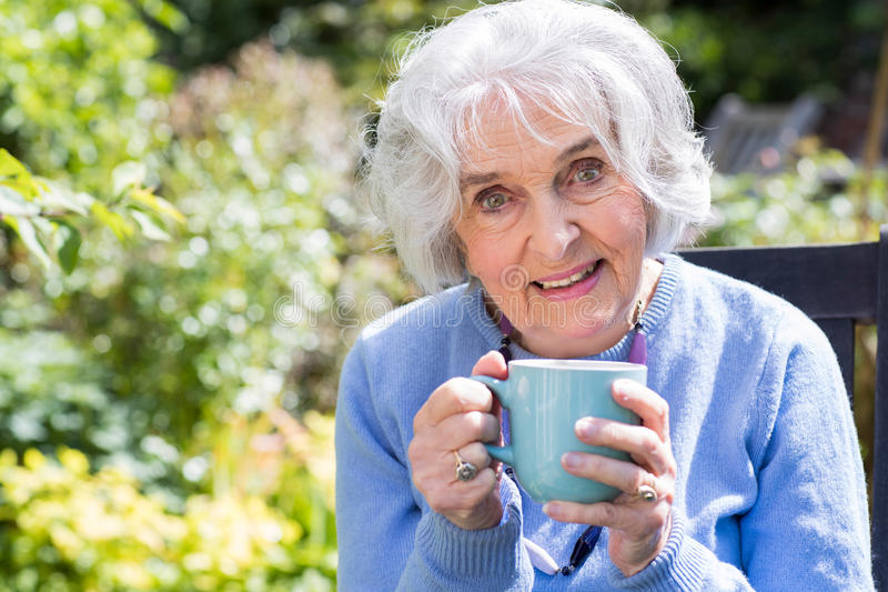 Portrait Of Senior Woman Relaxing In Garden With Hot Drink stock photography