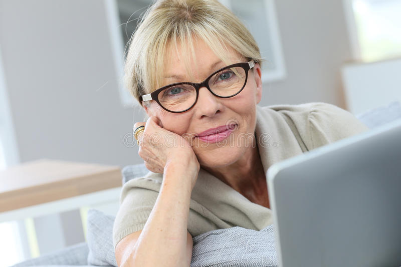 Portrait of senior woman relaxing in sofa websurfing on tablet royalty free stock image