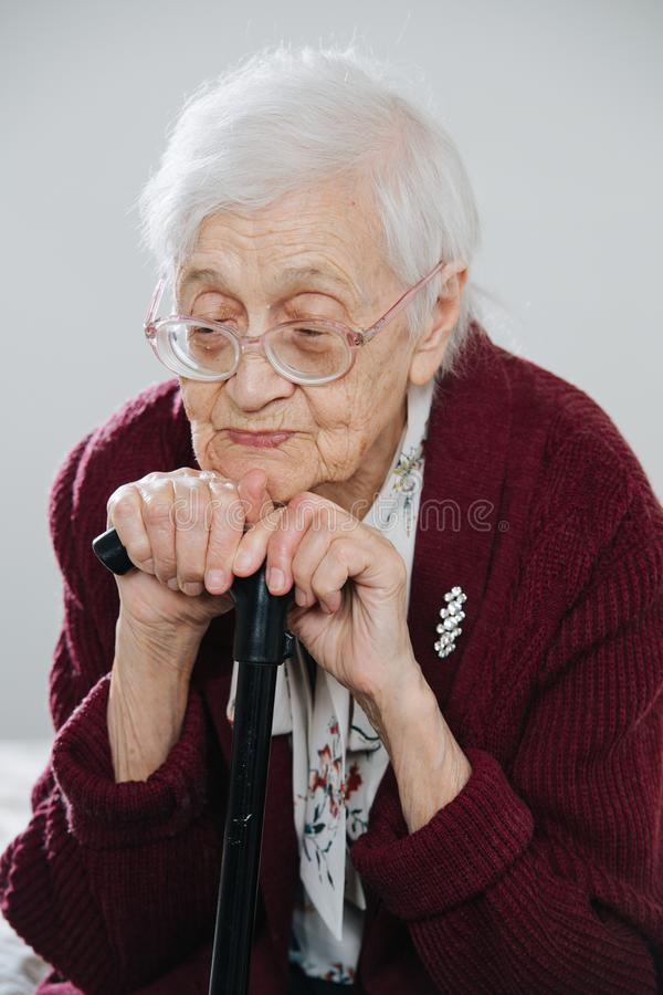 Portrait of a senior woman sitting on bed with walking stick at home stock images