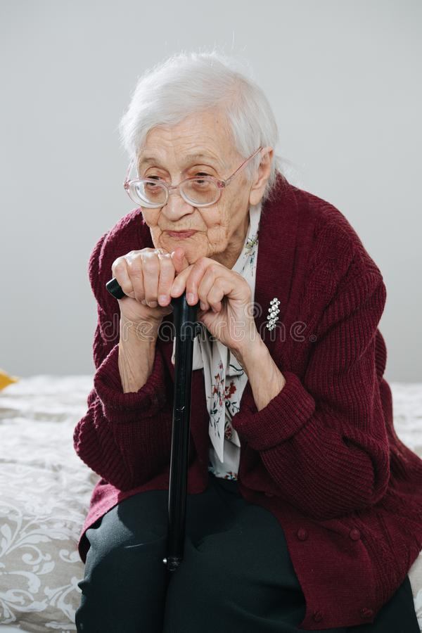 Portrait of a senior woman sitting on bed with walking stick at home royalty free stock photography