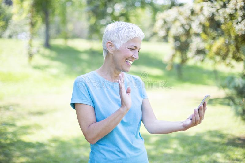 Portrait of senior woman in sports clothing using smart phone outdoor royalty free stock photography