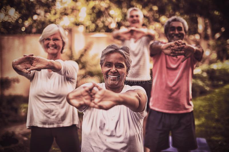 Portrait of senior woman stretching arms with friends stock images