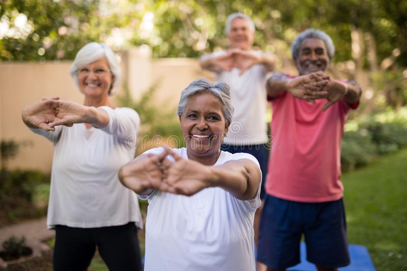 Portrait of senior woman stretching arms with friends. Portrait of senior women stretching arms with friends while exercising at par royalty free stock photo