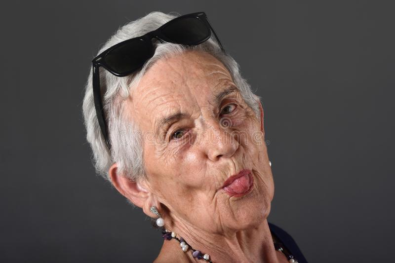 A Portrait of senior woman with tongue, royalty free stock image