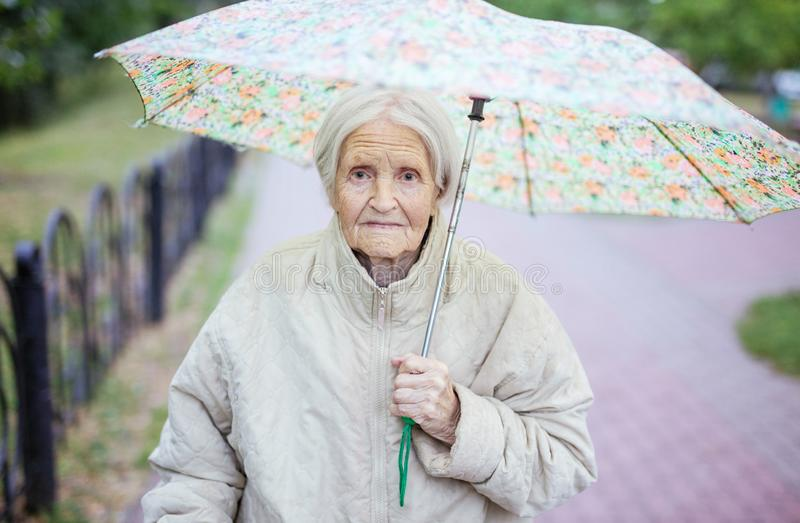 Portrait of senior woman under umbrella. Outdoors stock photos