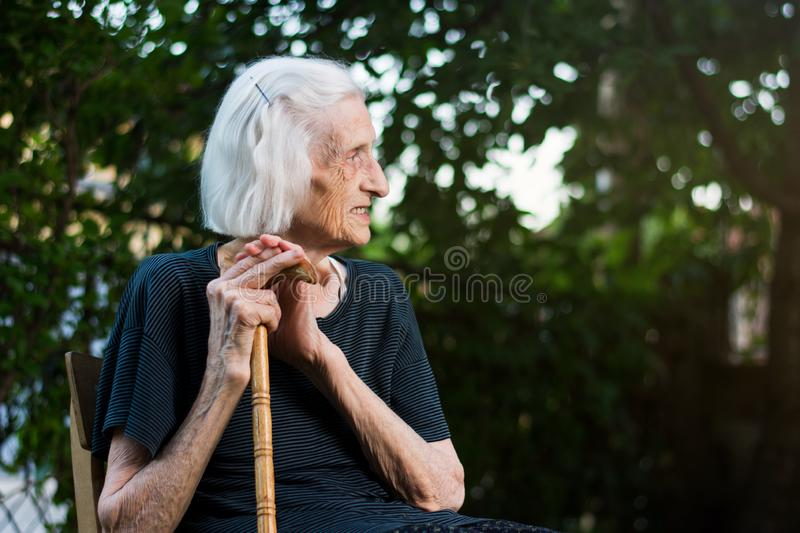 Portrait of a senior woman with a walking cane. Outdoors grandma stick sitting caucasian chair person old yard close aged aging backyard cheerful elder elderly stock image