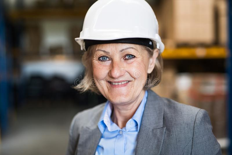 Senior woman warehouse manager or supervisor with white helmet. royalty free stock photos