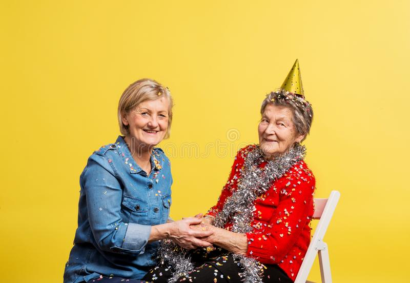 Portrait of a senior women in studio on a yellow background. Party concept. stock photography