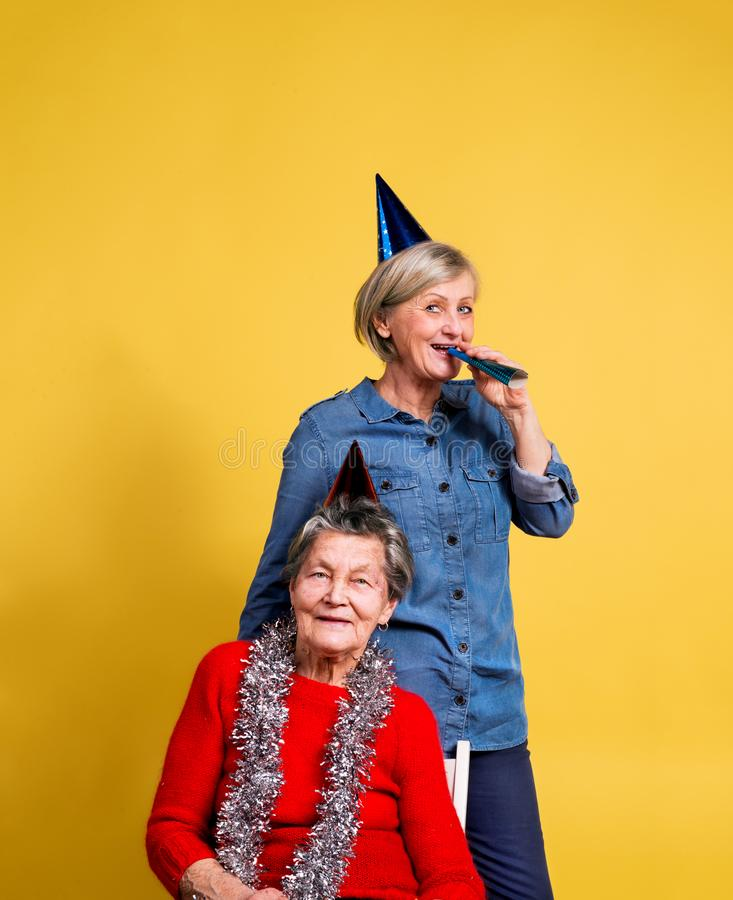 Portrait of a senior women in studio on a yellow background. Party concept. royalty free stock images